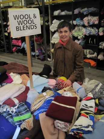 My fabric table at the annual Textile Center fabric garage sale, wearing a coat I made.