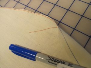 A practice aid: mark a bold line at 1/4 inch for guiding a consistent amount of fabric into the rolled hem scroll.