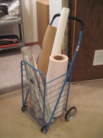 A cart used for farmers' market shopping now stores rolls of paper and a pad for ironing.