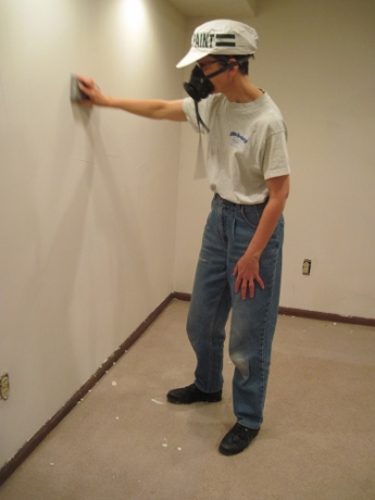 Wearing a dust mask, I used a sanding sponge to smooth the skim-coated walls.