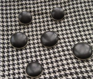 Black rounds edged in white, in two sizes. Big ones for the front closure, smaller for pocket trim?