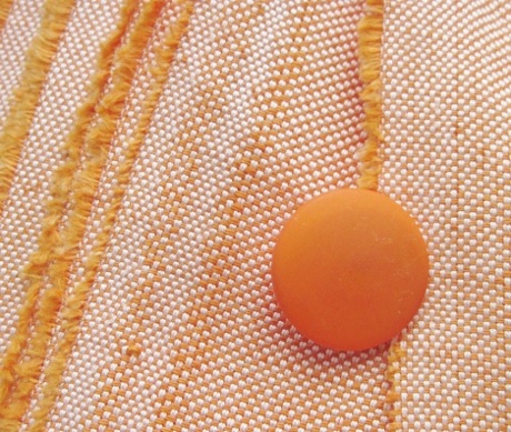 This orange button and its eight mates have been languishing on the wrong-color fabric for years. This is a much better combo.