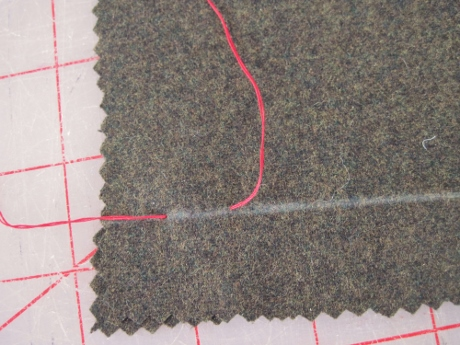 The beginning of a tailor tack, shown on a plain scrap.