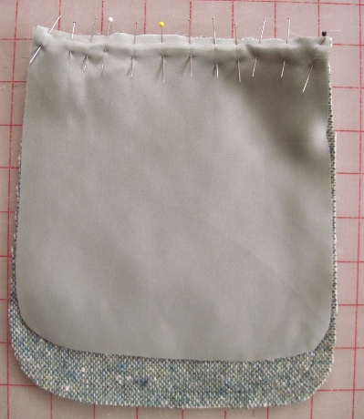 The lining is cut a little smaller so that the fashion fabric will automatically curl toward the back. The lining is stitched to the top, leaving a space to turn the pocket right side out.