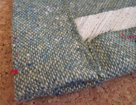 The overlap is catch stitched to the hem, but--surprise--the bottom fold is not slipstitched.
