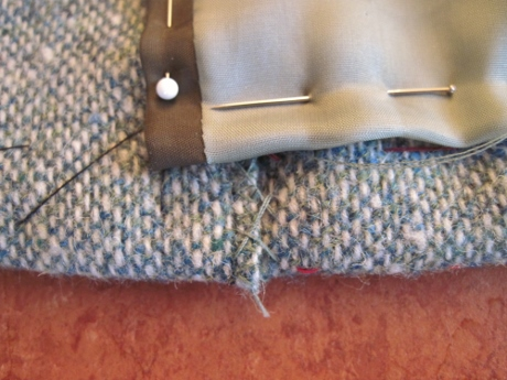 The exposed, raw edge of that little stretch of facing is traditionally secured with catch stitches.