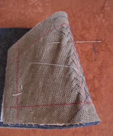 The ends of the undercollar are pad stitched curved over the hand to shape them.