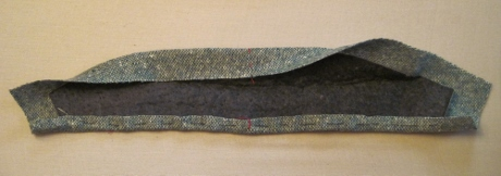 Now the neck edge of the upper collar is wrapped snugly around the undercollar and pressed in place.