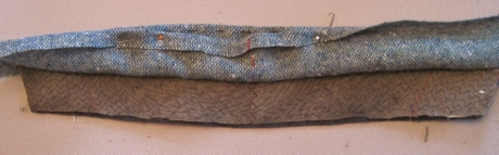 The canvas has been trimmed, although less than neatly,by 1/8 inch so that the collar felt is longer.