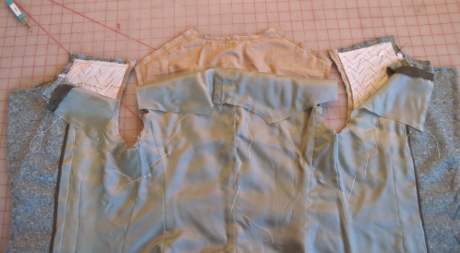The lining is moved out of the way before the shoulder seams are stitched.
