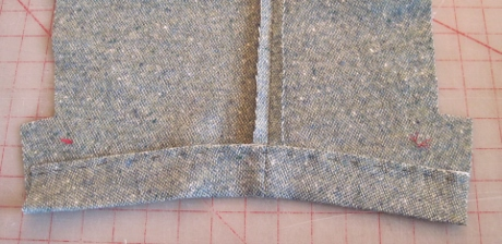After being interfaced the hem is turned up. It's curved, and the bias-cut canvas fits nicely in the curve.