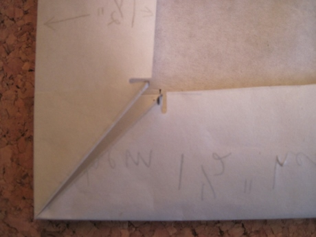 The paper is refolded to create the miter.