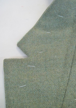 The undercollar and front are a single piece, removing a seam and therefore bulk. Notice--no seamline between undercollar and front. The line of stitching is holding the stay tape along the roll line.